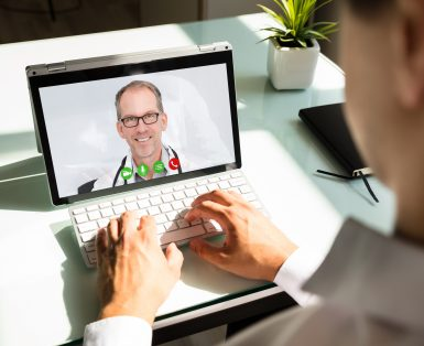 Businessman's hand videoconferencing with happy doctor on laptop