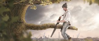 A man is sitting on a branch he is about to cut off. The background shows an industrial area which is polluting the surroundings. Thus the image conveys a secondary meaning towards environmental pollution.