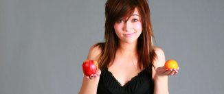Woman holding an apple and an orange.