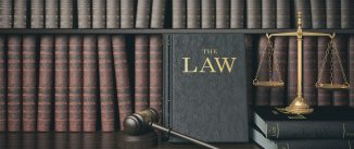 Law bookshelf with wooden judge's gavel and golden scale