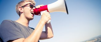 Young caucasian man screaming with a megaphone on the top of a hill during a sunny day.
