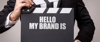 Hello My Brand Is written on a clapperboard holding by a executive