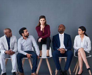Studio shot of a group of corporate businesspeople waiting in line against a gray background