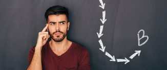 Man thinking hard in front of chalkboard showing dotted line ending at point B