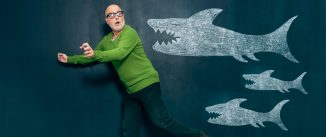 Man running away from three sharks drawn on a chalkboard