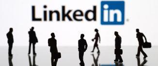 Human figurines standing in front of Apple iPad monitor displaying LinkedIn logo.